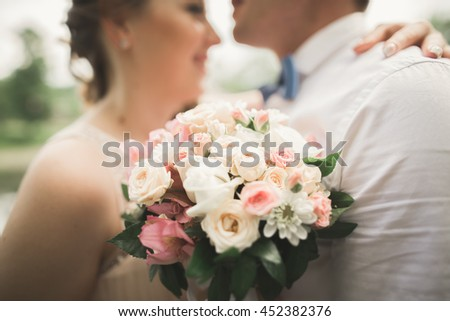 Bride and groom holding beautiful wedding bouquet. Lake, forest - stock photo
