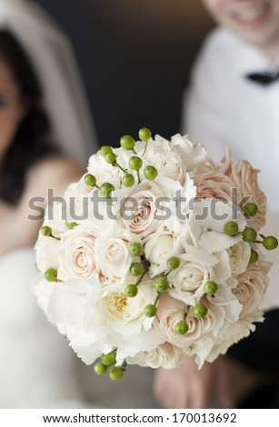 Bride and groom holding beautiful white wedding bouquet