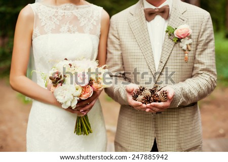 bride and groom holding bouquet and pinecones
