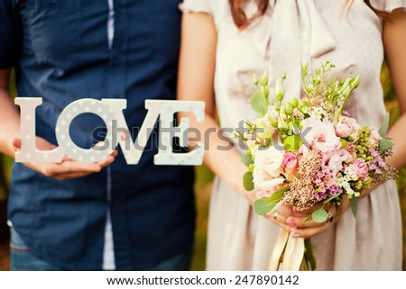 bride and groom holding bouquet and wooden word love - stock photo