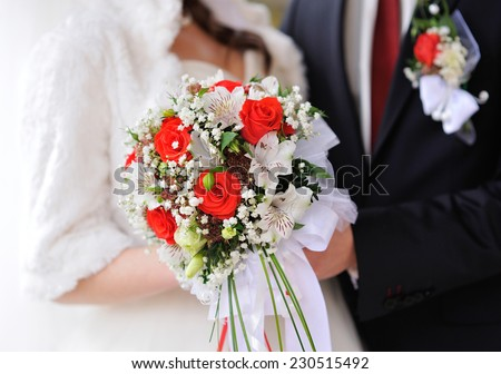 Bride and groom holding bridal bouquet close up. - stock photo