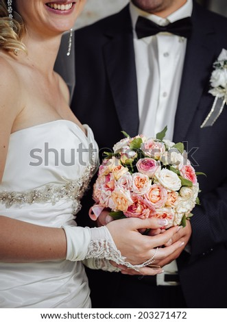 Bride and groom holding bridal bouquet close up. Detail of bride's roses bouquet and hands holding. - stock photo
