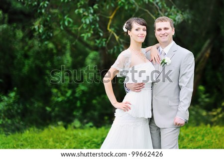 Bride and Groom holding each other in a park - stock photo