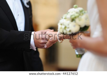 Bride and groom holding each other's hands during wedding ceremony - stock photo