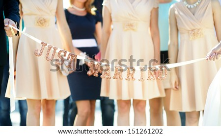 """Bride and groom holding glittering """"Just married"""" sign - stock photo"""