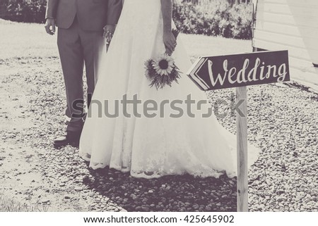 Bride and groom holding hand behind wooden wedding sign. Image in vintage black and white. - stock photo