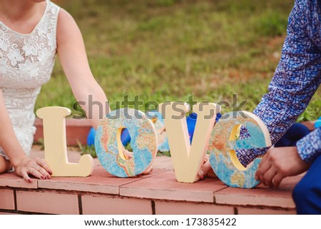 bride and groom holding handmade map LOVE letters - stock photo