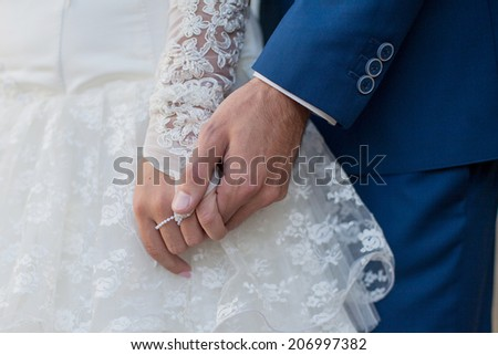 Bride and groom holding hands. - stock photo