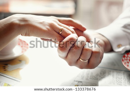 bride and groom holding hands in a cafe