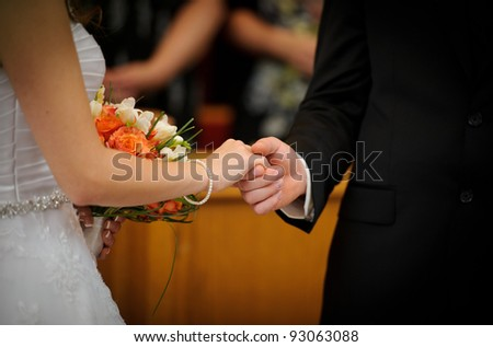 Bride and groom holding hands in church - stock photo