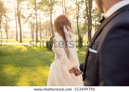 Bride and groom holding hands outdoors. Wedding theme, holding hands newlyweds