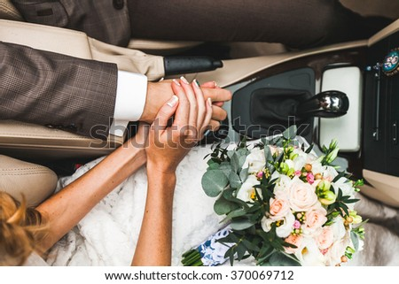 bride and groom holding hands while sitting in the car on the wedding day - stock photo