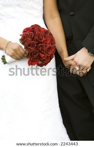 bride and groom holding hands with bouquet of red roses - stock photo