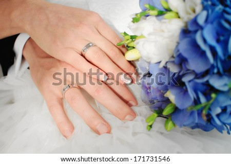 bride and groom holding hands with wedding rings - stock photo