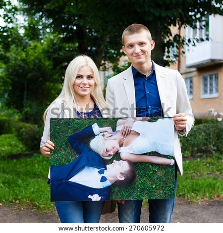 Bride and groom holding print after wedding day - stock photo