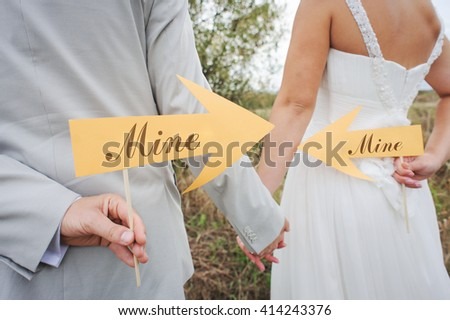 """bride and groom holding signs with """"mine"""" words - stock photo"""
