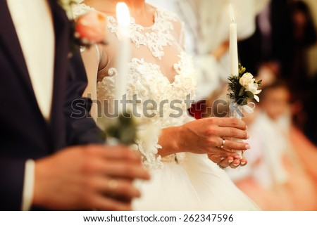 Bride and groom holding the candles. Close up. - stock photo