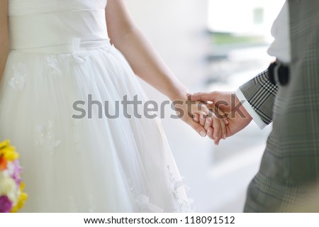 Bride and groom holding their hands - stock photo