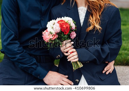 Bride and groom holding wedding bouquet together . Hug . beautiful hair - stock photo