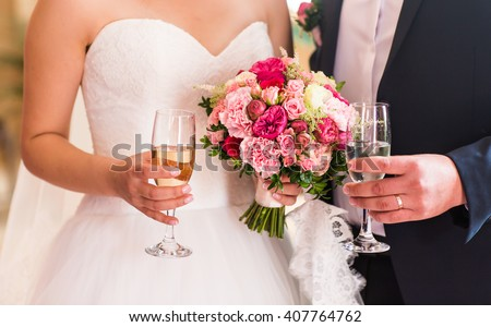 Bride and groom holding wedding champagne glasses close-up