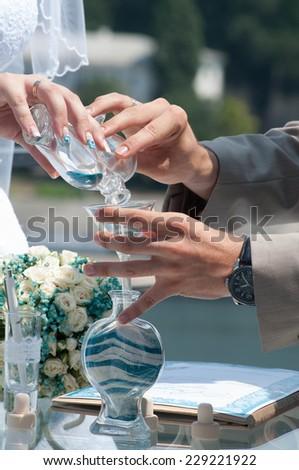 Bride and groom holding wedding symbol - stock photo