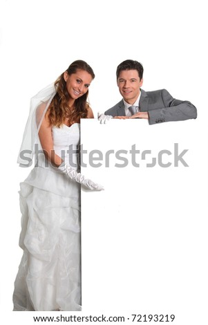 Bride and groom holding whiteboard - stock photo