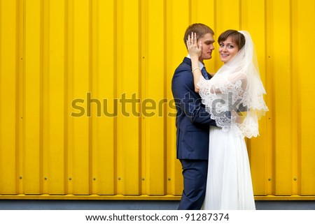 Bride and groom hugging against yellow wall - stock photo