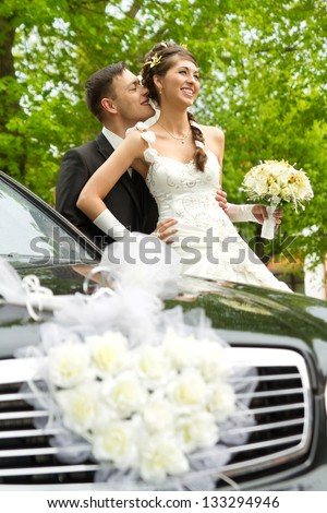 Bride and groom hugging and kissing outside. Wedding couple portrait