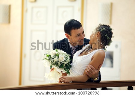 Bride and groom hugging and looking at each other outdoors indoors