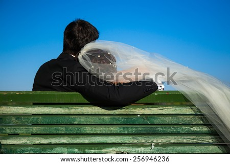 Bride and groom hugging in a bench - stock photo