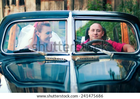 bride and groom in a retro car outdoor