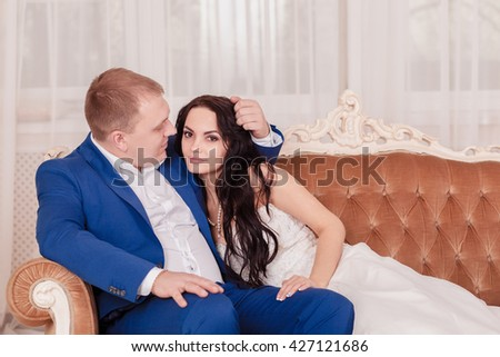 Bride and groom in luxury hotel, kissing on a sofa toogether