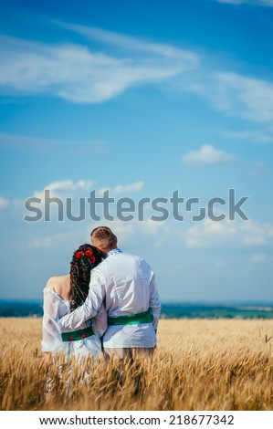 Bride and groom in national ukrainian clothes on the wheat field. ukrainian boy and girl in the wheat field.