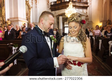 Bride and groom in the church exchanging the rings - stock photo