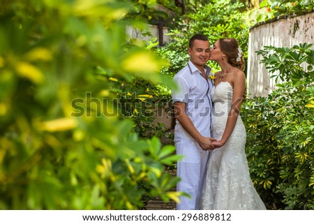 Bride and groom in the garden together. - stock photo