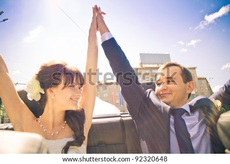 bride and groom in wedding car - stock photo