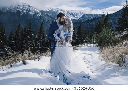 Bride and groom in winter snow on mountain - stock photo