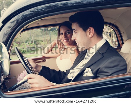 Bride and groom inside a classic car. They are happy. - stock photo