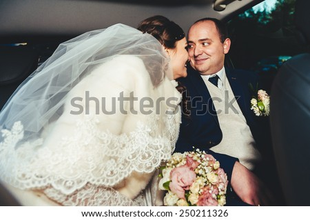 Bride and groom inside a classic car. They are happy. portrait of the happy bride and groom in the car. - stock photo