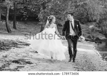 bride and groom is jumping with joined hands to the sunset  - stock photo