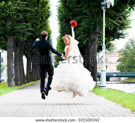 bride and groom is running with joined hands on city park road - stock photo