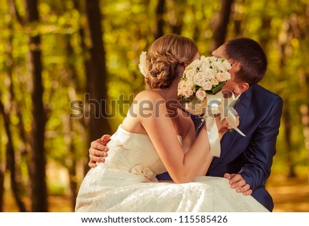 bride and groom kissing behind wedding bouquet - stock photo