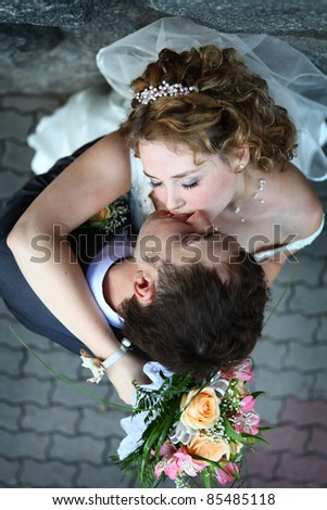 Bride and groom kissing near stone wall - stock photo