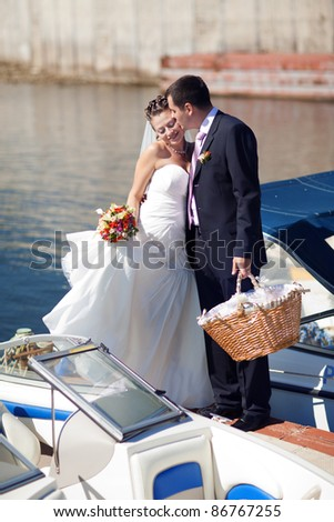 bride and groom kissing on the pier - stock photo