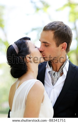 Bride and groom kissing outdoors in the park - stock photo