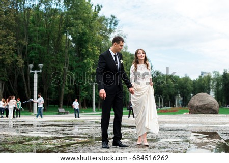 Bride and groom kissing with the fountain on the background