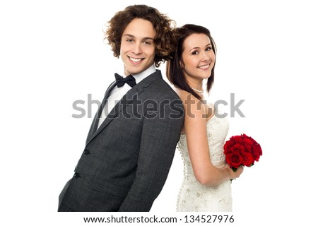 Bride and groom leaning on each other, back to back. - stock photo