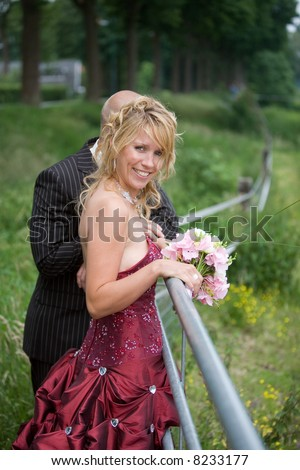 Bride and groom leaning over a meadow fence