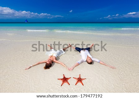 Bride and Groom lying on beach shore with two red starfish - stock photo