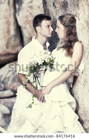 Bride and groom near the rock. Tropical wedding - stock photo